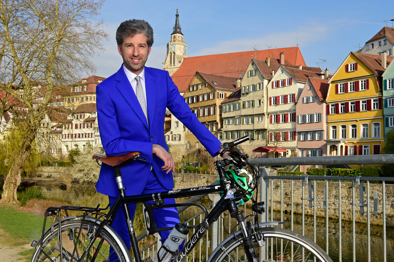"""Boris Palmer mit Fahrrad auf der Neckarbrücke  Das Bild entstand zum Auftakt der städtischen Klimaschutzkampagne """"Tübingen macht blau 2.0"""" im April 2016.  Bild: Gudrun de Maddalena"""